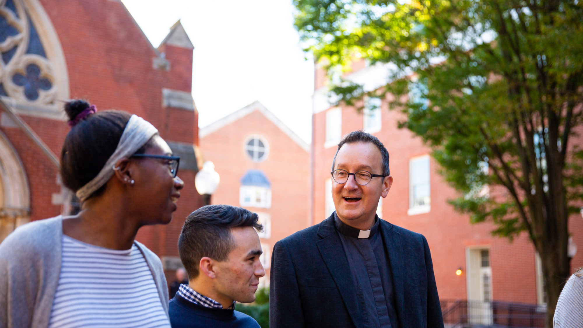 Two students talk with Fr. Bosco in Dahlgren Quad.