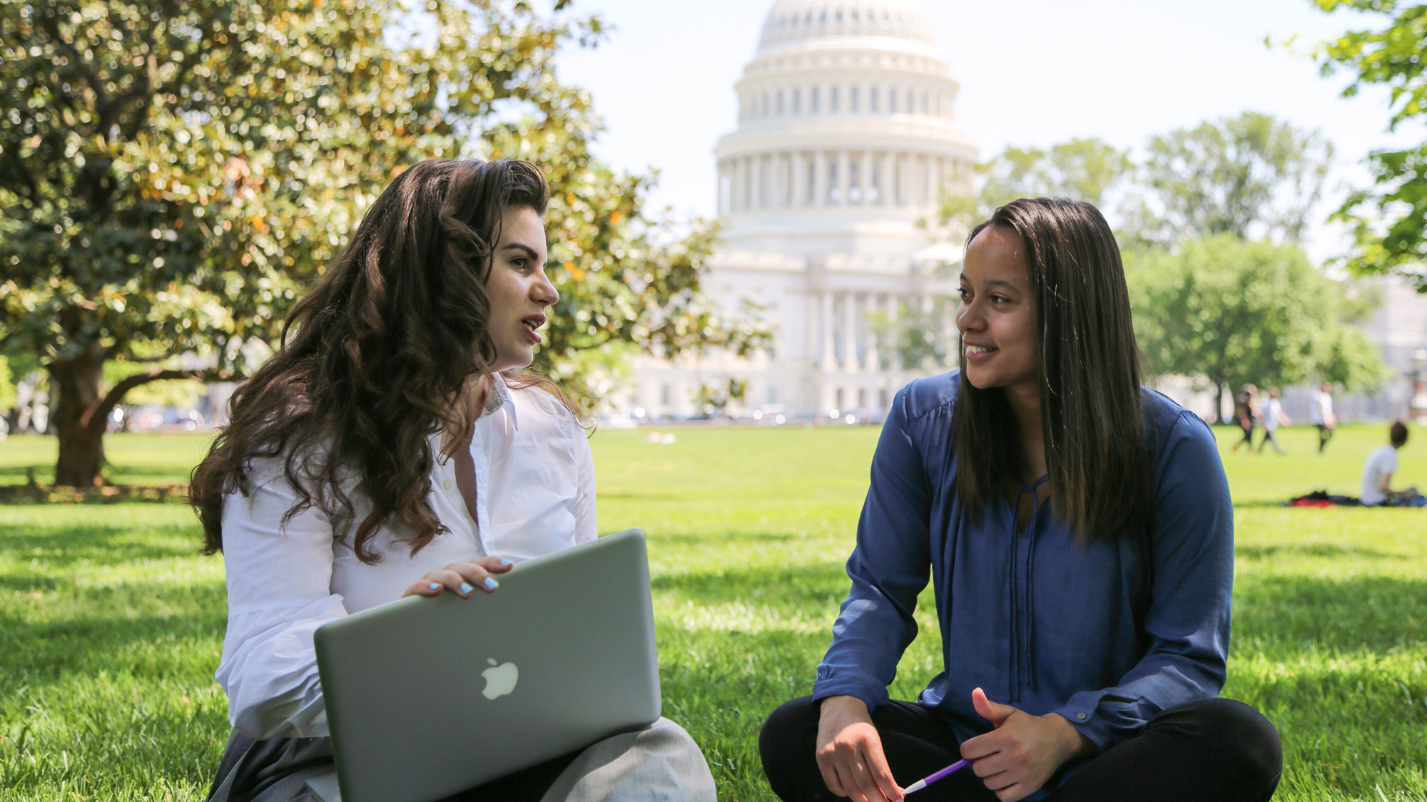 Two students work on laptops next to the Capitol Building.
